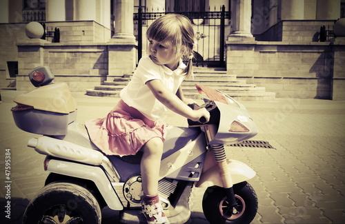 Fototapete Biker little  girl on a motorcycle