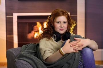 Teenage girl sitting at home at fireplace