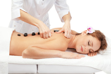 beautiful woman in spa salon with spa stones  getting massage,