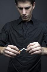 Young man breaks a cigar