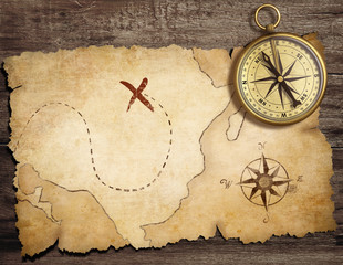 Wall Mural - aged brass antique nautical compass on table with old treasure m