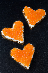 Sandwiches with red caviar in the form of heart