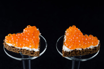 two sandwich with red caviar in the form of a heart
