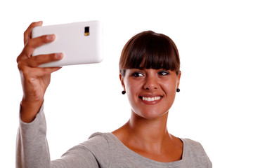 Smiling young woman taking picture with cellphone