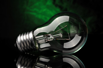 Light bulb on black green background