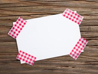 Zettel mit 4 Klebestreifen rot-weiss auf Holz