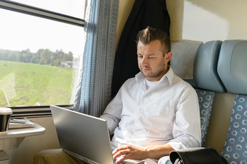 Man commuting with train using laptop travel