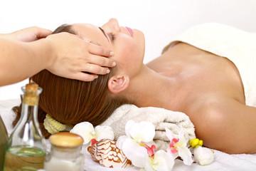 Relaxed young lady getting facial massage at spa salon