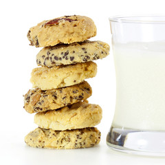 a stack of mixed fruit cookies and glass of milk