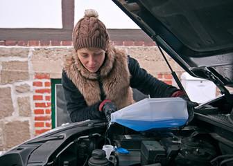 Frau kippt Frostschutz auf