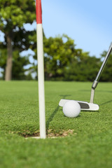 putter puts a golf ball to hole on green of golf course