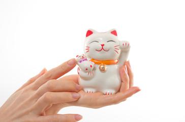 女性の手と招き猫