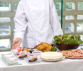Female chef showing a lot of cooked food and bakery.