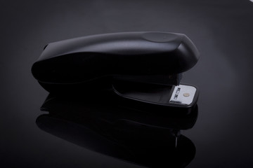 photo  of a stapler on a black shiny background