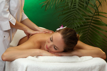 beautiful young woman in spa salon getting massage,