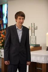 Konfirmant vor dem Altar der Kirche