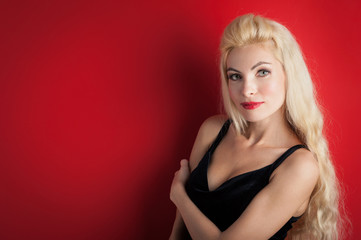 Beautiful blonde woman close up portrait against red background.
