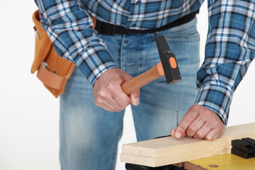 male hands hammering nail