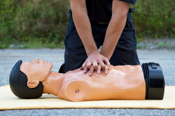 Male instructor showing CPR on training doll
