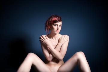 Schöne nackte Frau vor blauem Hintergrund
