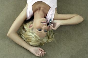 Liegende Frau telefoniert mit Handy