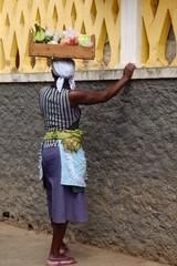 Femme africaine portant un cageot sur la tête.