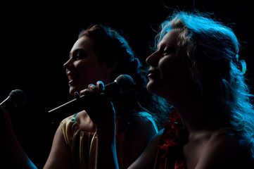 Two women singing in microphone