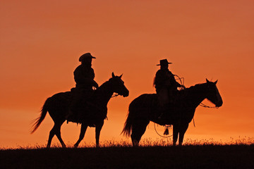 Cowboys on Horseback Silhouette at sunset