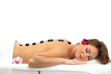 beautiful young woman in spa salon with spa stones, isolated