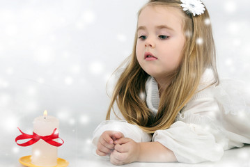 A beautiful little girl angel with a candle