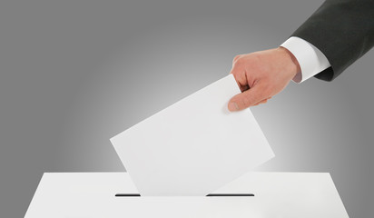 Man hand down the ballot in the ballot box