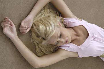 Junge blonde Frau relaxed auf einem Teppich