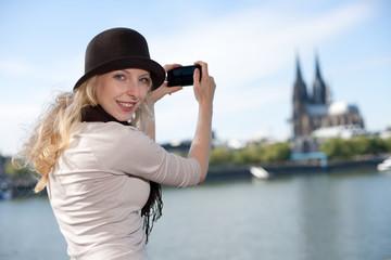 Frau fotografiert den Kölner Dom