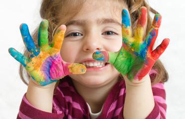 niña preescolar con las manos pintadas