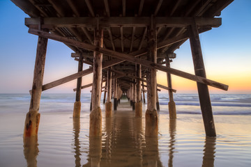 Under Newport beach pier at sunset
