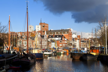 Fototapete - sunny canal in Groningen with many river boats