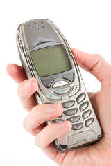 An old worn out cell phone being held over white