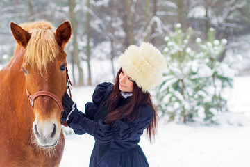 Beautiful woman and horse in winter
