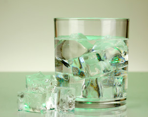 Ice cubes in glass on light green background