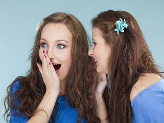 two young female friends whispering gossip