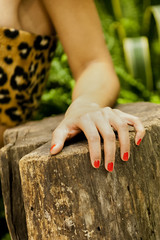 A female woman hand with red nails leaning on wood