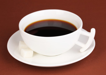 A cup of strong coffee on brown background