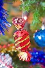 new-year toy a candy hangs on a christmas tree