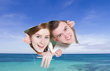 young couple looking though hole at tropical sea - concept shot