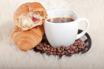 Croissant with coffee and beans on fur background