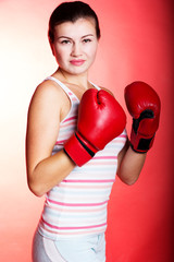 Attractive young woman wearing red boxing gloves