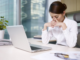asian businesswoman sitting and thinking in office