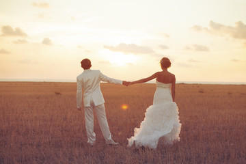 bride and groom posing in field with yellow grass on sunset
