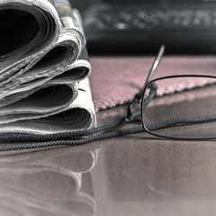 pile of newspaper & glasses