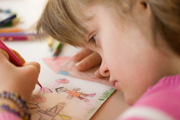 Close up of a girl with down syndrome drawing.